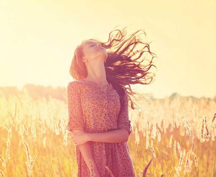 image d'une femme les cheveux au vent détendue apaisée présente à son corps
